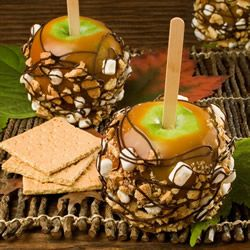 "S'mores Apples | ""Caramel apples are studded with graham crackers and marshmallows and drizzled with chocolate for a treat you can't get enough of."""