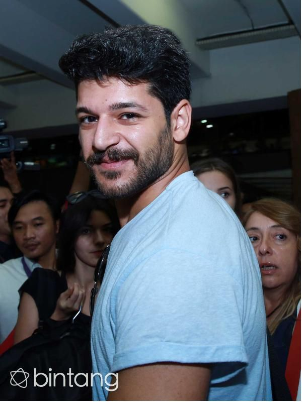 Aktor tampan asal Turki Emre Kivilcim yang berperan sebagai  Selim dalam serial 'Elif' tersenyum ramah saat tiba di Bandara Soekarno-Hatta (23/8/2015). #Elif #Selim #EmreKivilcim #Bintang #Indonesia