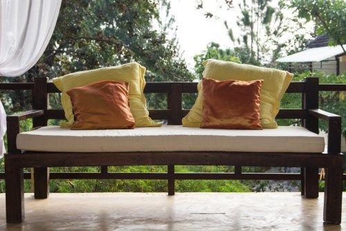 Деревянная скамья в саду с подушками.