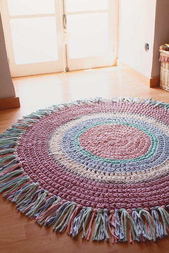 Afombra Multicolor con Flecos Tamaño: 1.20 metros de diámetro incluyendo flecos. Los colores utilizados son: -Rosa bebé -Azul bebé -Gris -Verde agua -Malva -Blanco Los flecos están hechos con tres colores diferentes. Lavar preferentemente a mano.