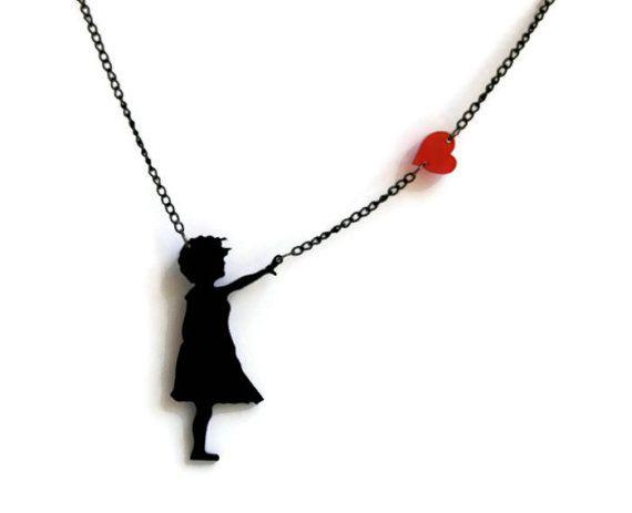 Le très populaire et emblématique Banksy petite fille avec coeur de flottement de style dans un pendentif avec chaîne noir anodisé. Un Brand New et