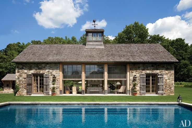 Designed by architect Gil Schafer, decorated by John Cottrell, and landscaped by Deborah Nevins, a Connecticut poolhouse takes the shape of a sophisticated barn with stone walls and weathered plank shutters.