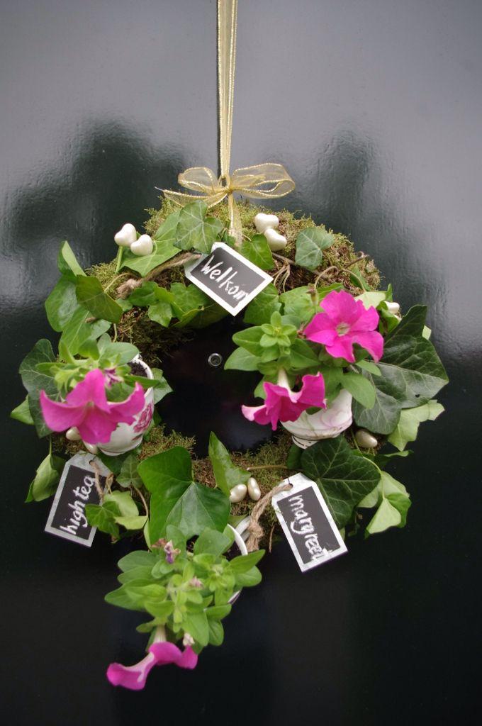 Krans met oude theekopjes met plantjes en andere versieringen als welkom op de high tea