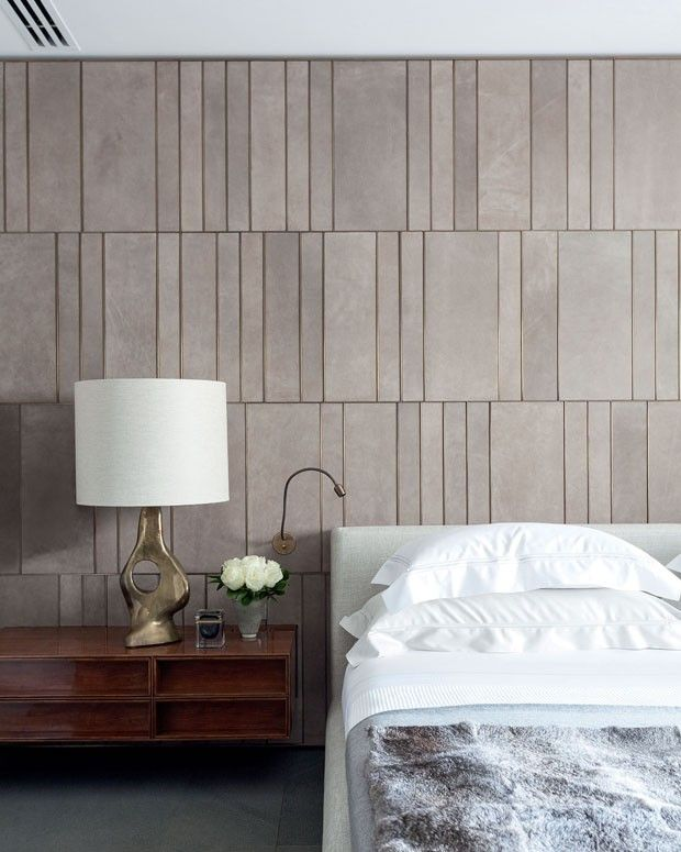 Linear suede and brass wall against organic brass lamp in this luxury bedroom: Kiko Salamao, São Paulo