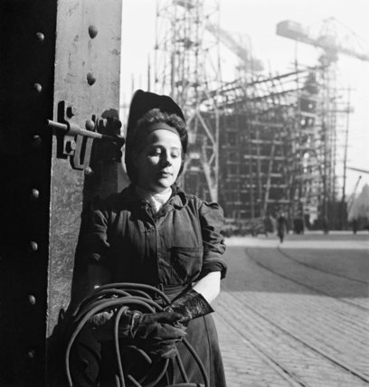 A study of a young woman welder . She is posing for the photographer, leaning against a column. In the background a ship under construction can be seen in a slipway.  Beaton Cecil  © IWM (DB 62)