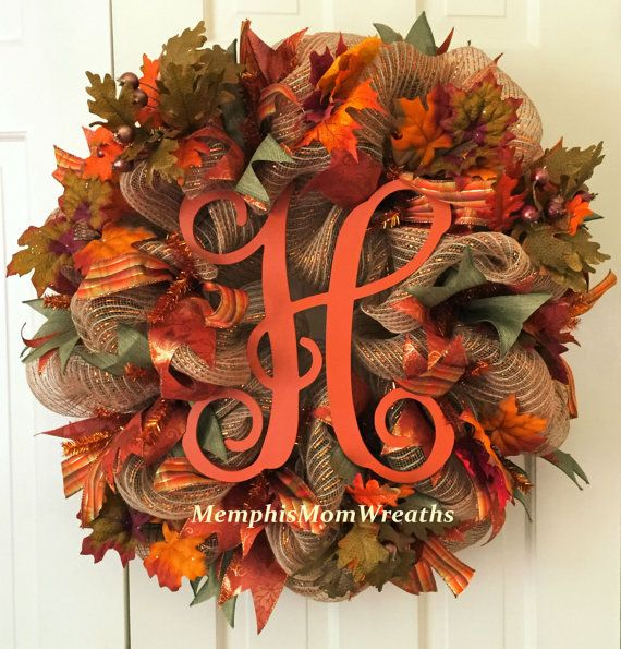 Make a graceful transition to fall with this gorgeous Fall Monogram Burlap Deco Mesh Wreath! You choose the letter, and well make a gorgeous custom monogram wreath just for you!  This 26 diameter wreath features 21 burlap with metallic copper stripe deco mesh, 3 moss green canvas ribbon, 3 russet leaf print ribbon, and 1.5 plaid ribbon. Fall leaf picks surround 12 x 11 russet monogram of your choice. Double doors? Love the look for prefer a different color on the monogram? We can design a…