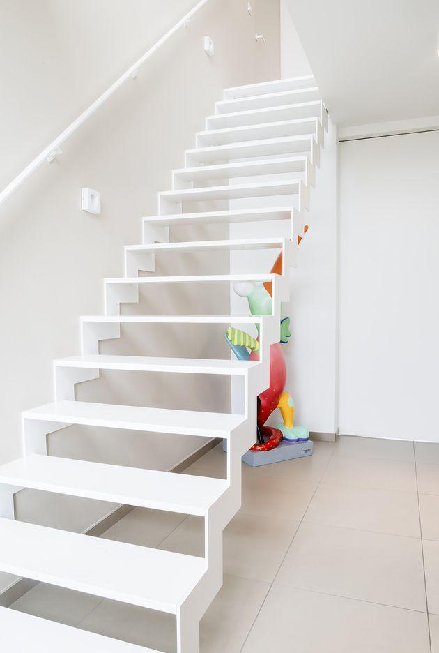 Stalen trap met Corian treden en strakke armleuning langs de muur. Door Corian te gebruiken voor de treden wordt een stil en onderhoudsvriendelijk loopvlak gecreëerd dat eveneens warmer aanvoelt dan staal!