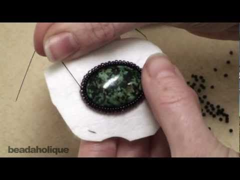 http://www.beadaholique.com/yt - In this video learn how to bead embroider a bezel row around a cabochon. This technique adds extra depth to your work and makes it so the cabochon looks more set down into, and encased, in beads.  Bead Embroidery http://www.beadaholique.com/t-ba-videos-bead-embroidery.aspx?utm_source=YouTube_medium=social-med...