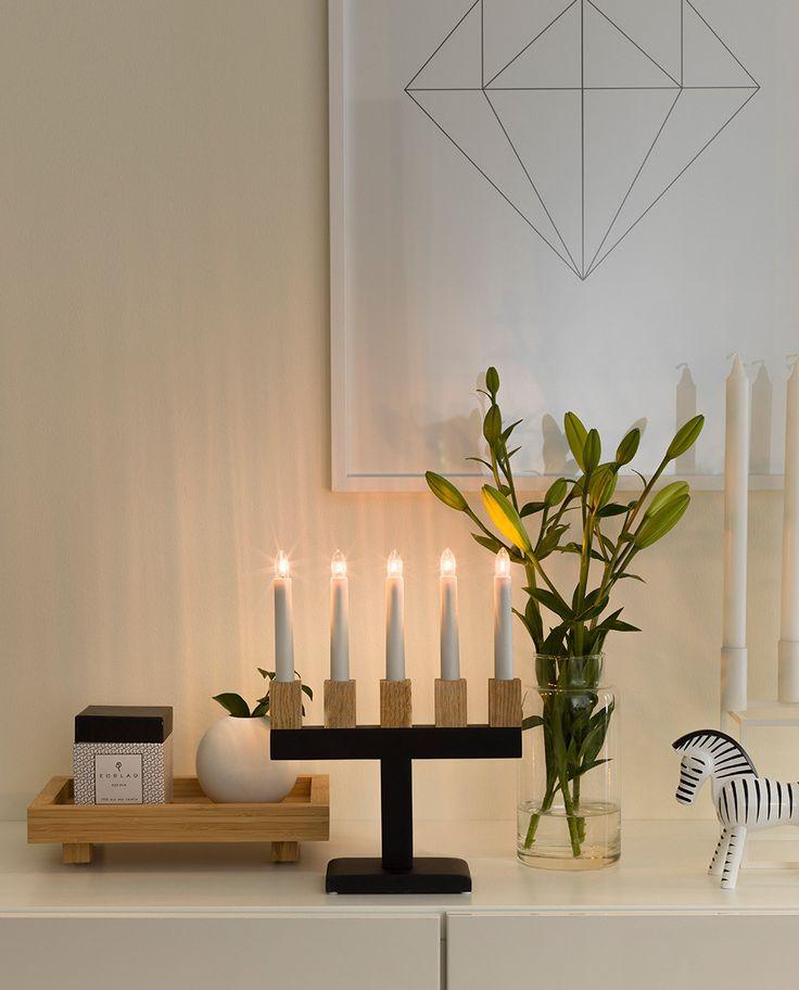 Adventsstake i sortlakkert treverk med detaljer i eik og 5 hvite stavlamper fra Konstsmide. Staken har en meget ren og rett design og den lyse eikefargen komplimenterer godt den sorte staken.