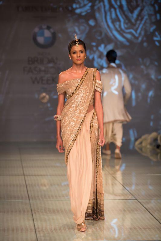 Tarun Tahiliani gold shimmering sari with off the shoulder blouse. More here: http://www.indianweddingsite.com/bmw-india-bridal-fashion-week-ibfw-2014-tarun-tahiliani-show/
