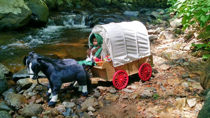 """The official Little House on the Prairie® doll wagon is perfect for imaginative play. It has working wheels, a removable canvas cover and a seat big enough for two 18"""" dolls to sit side by side."""