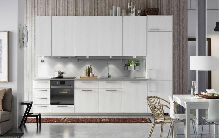 Cocina blanca de diseño moderno con armarios blancos, frontales RÅSDAL de fresno blanco, encimeras blancas y electrodomésticos integrados