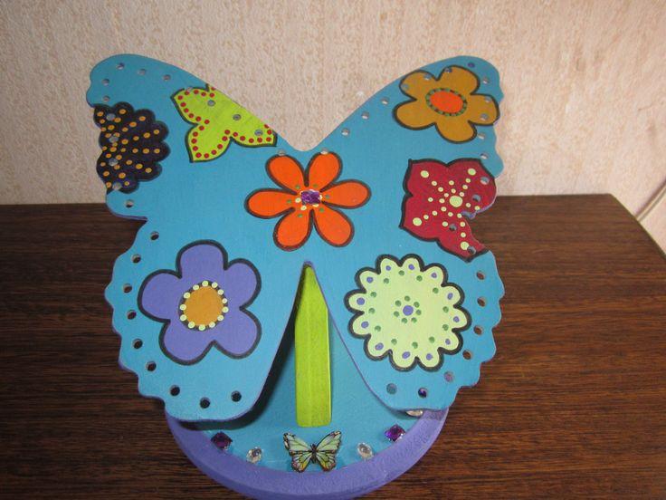 Porta Aros diseño Mariposa, decorada en pintura Alpa Arte tono calipso con variedad de flores en tonos alegres, pedestal en tono verde cata y base en tono calipso con bordes lila, aplicaciones en brillantes tono morado y plateado.  VALOR $4.000