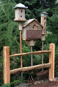 Recycled Garden Tools with Bird Houses made from reclaimed wood and objects on top built into a section of the fence!