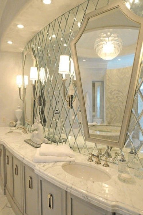 For similar effect buy small square mirrors turned on an angle and glue to wall then hang two large mirrors over them. Terrific!
