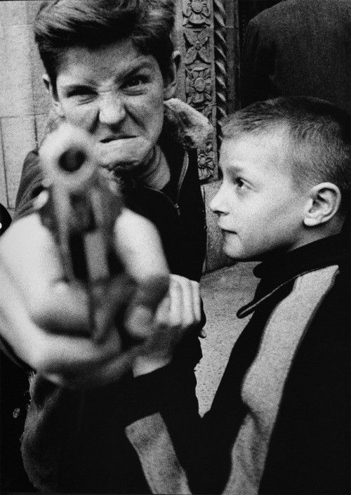The focal point is looking down the barrel of the gun which leads you looking at the boy's angry face. The younger child seems to be trying to stop the boy from shooting. From the angle Diane has taken the photo from it looks like the boys is pointing the gun towards her. There isn't a strong contrast in the photograph, there are more greys and blacks and the whites aren't as strong as what they could be. Diane demonstrates shallow depth of field as the gun isn't in focus and the background…