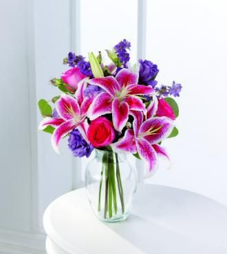 I love the idea of some sort of purple flower, white roses and stargazer lily, since stargazers are my favorite flower.  Something like this would be my first choice.