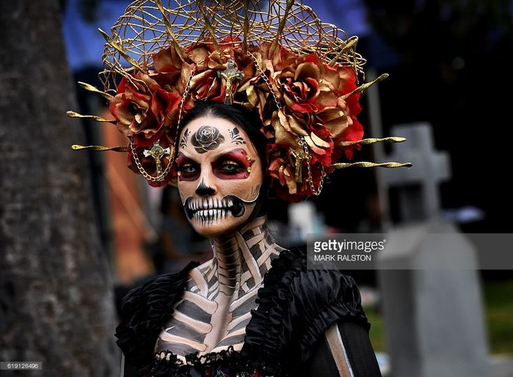 A woman dressed in a skeleton costume parades during the annual Dia de los Muertos (Day of the Dead) festival at the Hollywood Forever cemetery in Hollywood, California on October 29, 2016. Dia de los Muertos is a festival to remember friends and family members who have died and is celebrated throughout Mexico and by people of Mexican heritage living in the United States. / AFP / Mark RALSTON