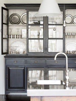 Dark china cabinet with light interior and glass doors. Love that it's in the kitchen.