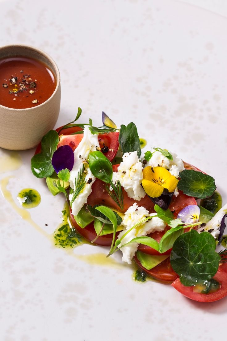 James Mackenzie adds an elegant flourish to a classic tricolore salad recipe, enhancing the simple combination of tomatoes, mozzarella and avocado with a fragrant lovage and pistachio pesto and a lightly spiced shot of chilled gazpacho. A vibrant avocado salad recipe with a refreshing tomato soup on the side.