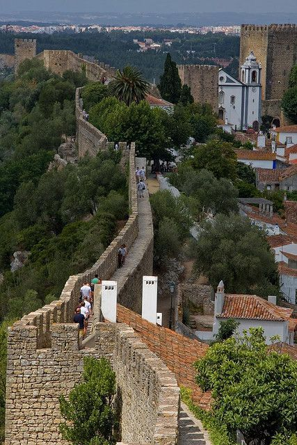 Walk on the walls of fortified village of Obidos, heading to visit the Medieval…