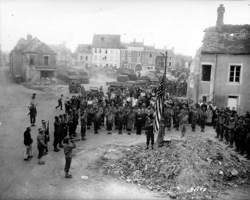 French civilians and US soldiers saluting the flag while celebrating the 4th of July—Independence Day—in Trévières.