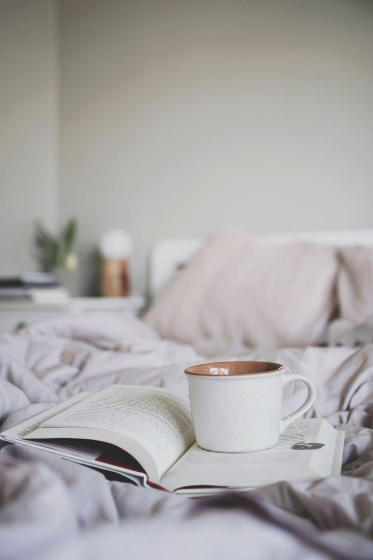 CHÁ NO MEU DIA-A-DIA E UM POUCO DE ASMR  Livro aberto na cama bagunçada com uma caneca do Snoopy em cima.
