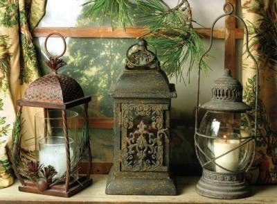 "Rustic Lanterns    Enduring, romantic iron lamps on three themes illuminate by flickering candlelight.  Pinecone. 12"".  Baroque. 12"".  Classic. 15""."
