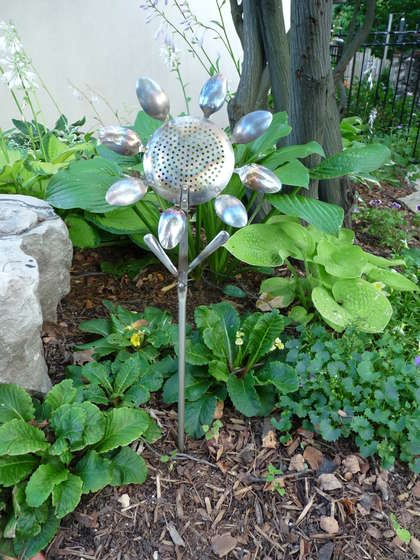Yard art flower made from spoons and a colander. Ingenious!