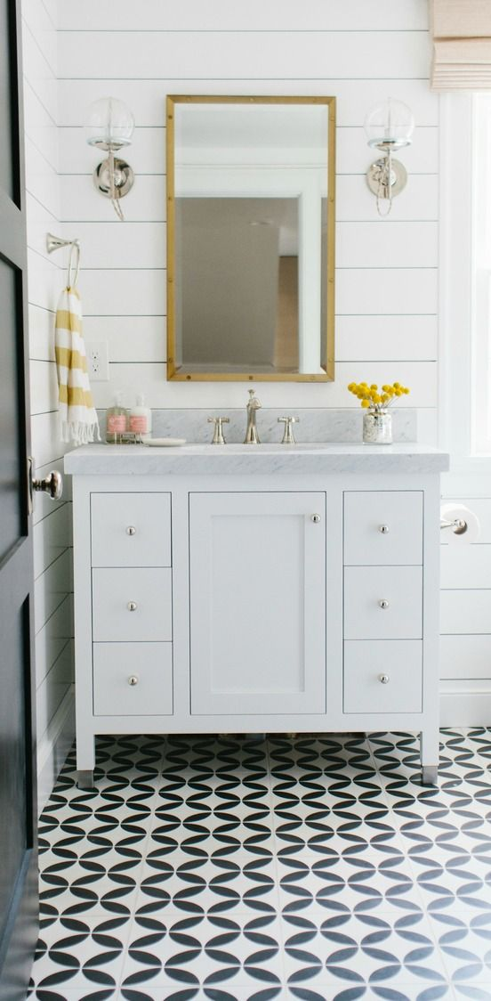 Check out the many different ways that you can use shiplap walls in your home with this post from Blogger Shea, of Studio McGee. Shea shows you a collection of rooms to demonstrate how truly versatile this timeless style trend is. This classic neutral bathroom uses bright white walls, bold black tile flooring, and pops of bright yellow for a modern and welcoming space.