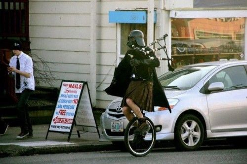 Darth Vader rides a unicycle in a kilt