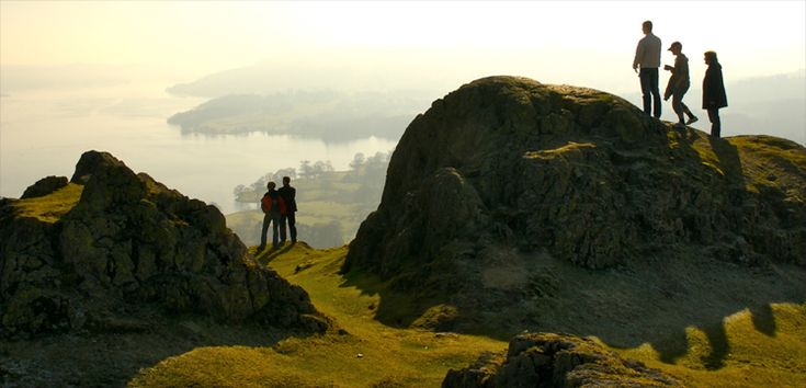 Home Page for Lake District National Park ....Walkers on Loughrigg fell overlooking Windermere