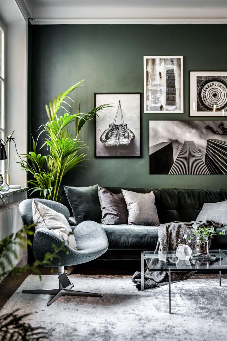 Grön soffa och fotölj i sammet mot ännu en grön vägg. Vackert