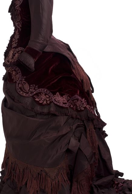 c1877 Two-piece claret-colored velvet and taffeta reception gown with bustle and train. Self-covered buttons at center front with detail embroidery. Asymmetrically trimmed with draped swags, knotted cotton fringe and self-fabric bows. Hand and machine sewn. 32 in (bust) 27 in (waist) 55 in (front length, not train) Item #6062.62 A,B See other pins for more views.