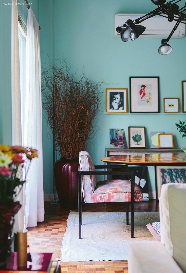 Uma sala de jantar linda, com parede verde-água, poltronas estampadas e muitos quadros apoiados em móveis e canaletas.