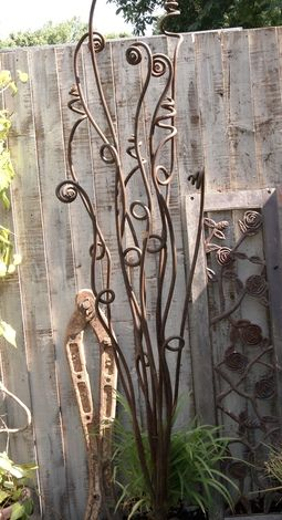 Metal ferns garden sculptures - I made vines on my garden shed and added metal flowers with this idea