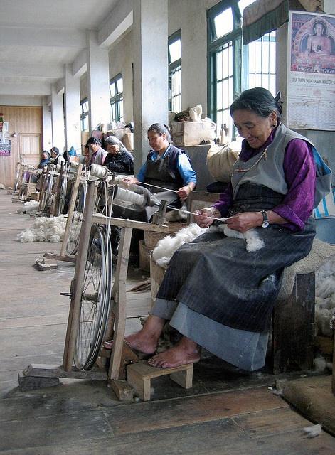 Spinning Wheels - Women in the Darjeeling Tibetan refugee centre, using spinning wheels to make thread from wool