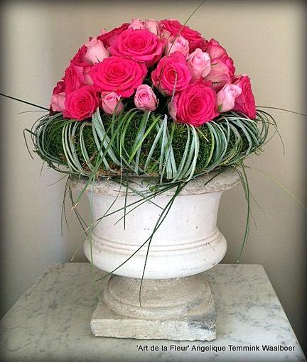 Prachtige robuuste pot met een krans en bloemstuk. De krans is opgestoken met platmos daarna omwikkeld met berengras. De biedermeier is volgestoken met 2 soorten rozen ( 40 stuks ) Gemaakt door Ciska bij 'Art de la Fleur'.