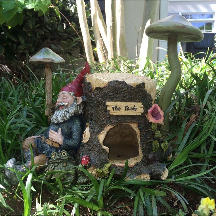 Toad House With Gnome Sleeping Against A Tree Stump With His Pet Toad