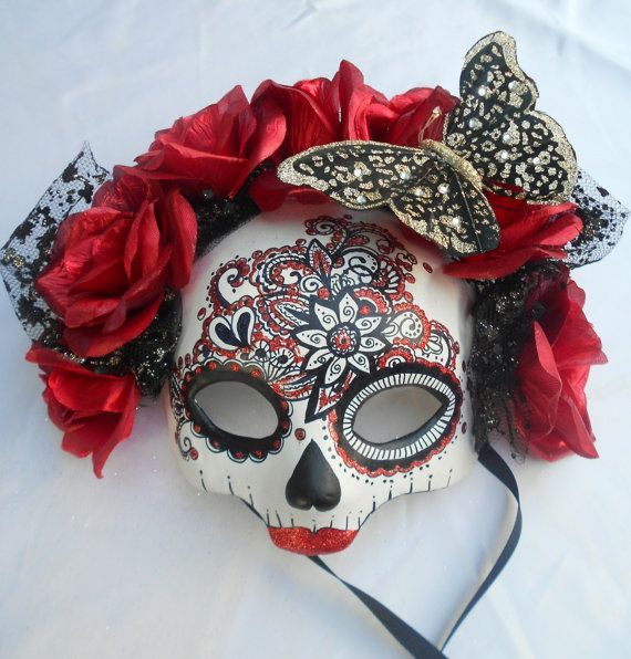 Beautifully hand painted Day of the Dead skull mask, hand formed out of light weight paper clay. Red silk flowers and a faux black butterfly frame