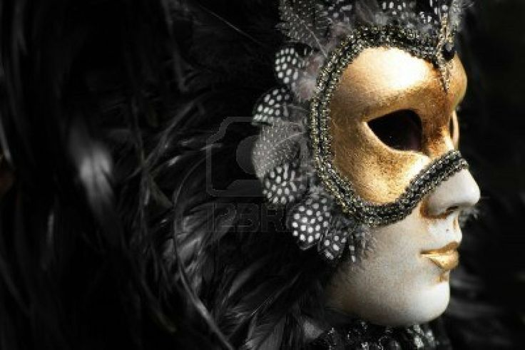 Venetian mask decorated with gold leaf and embedded with fowl feathers. Stock Photo
