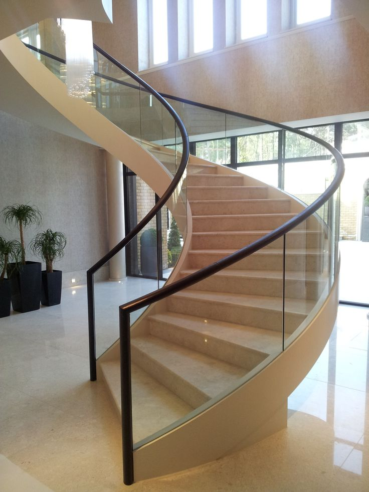 FABRICATED MILD STEEL HELICAL STAIRCASE WITH STRUCTURAL GLASS BALUSTRADE AND LEATHER CLAD HANDRAIL.