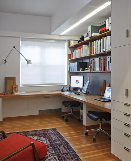 This take on the two-person office presents each person with less individual workspace but saves room for a joint counter near the window. Houzz users saved this photo for its smart layout and the industrial open shelving.