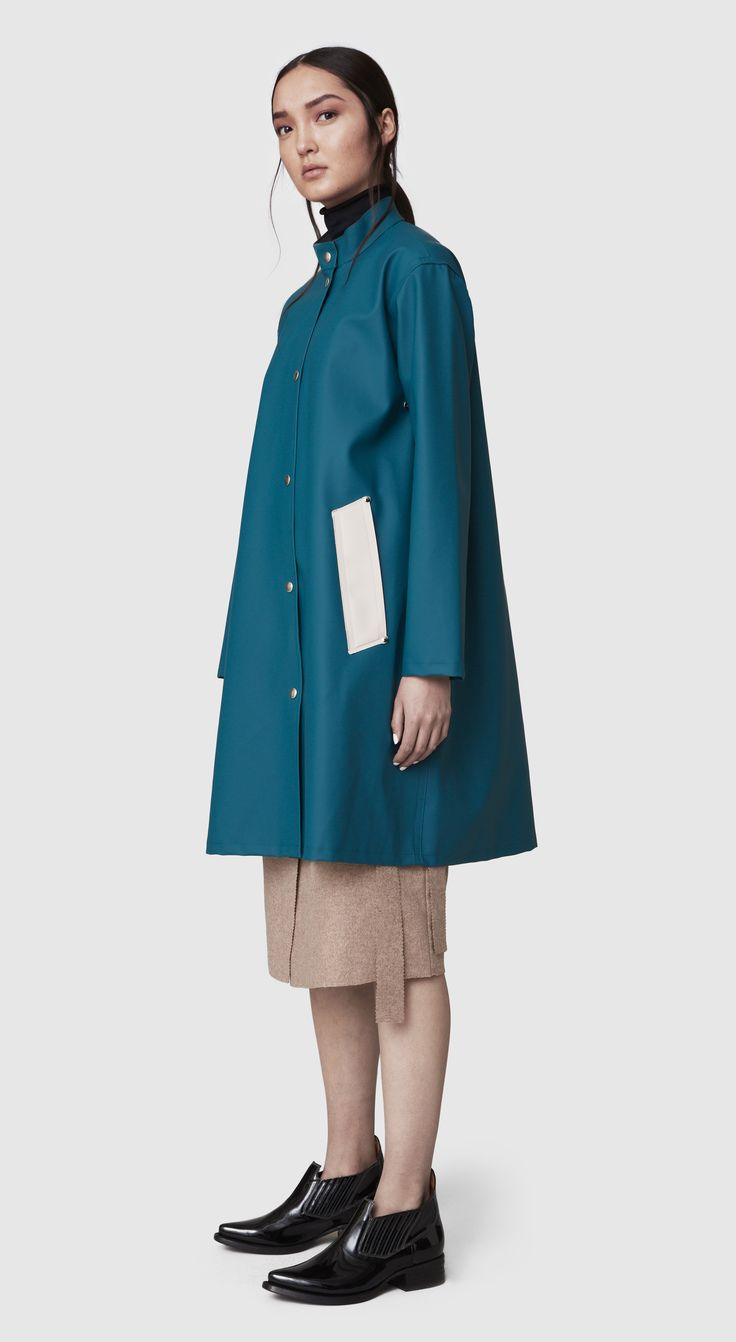 The Alvik Petrol Blue raincoat is our new women's A-lined shaped, hoodless raincoat in rubberized cotton. This feminine style is handmade and comes unlined and with welded seams. The finest craftsmanship is used to create this beautiful raincoat, here in