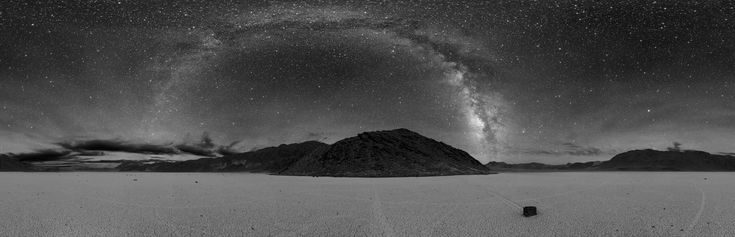 360° panorama of Racetrack Playa in Death Valley at night. The Milky Way is visible as the arc in the center. A sailing stone is also seen below along with the tracks of other stones.