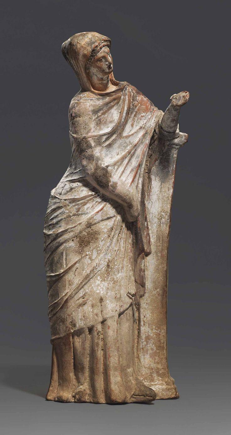A GREEK TERRACOTTA FEMALE FIGURE TANAGRA, HELLENISTIC PERIOD, CIRCA 3RD CENTURY B.C. Estimate GBP 8,000 - GBP 12,000 (USD 10,240 - USD 15,360)