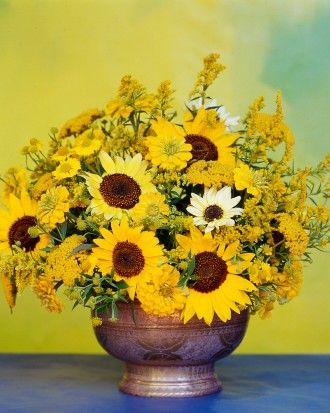 An ode to Van Gogh: a deep bowl mounded with a variety of garden sunflowers, along with yarrow, zinnias, goldenrod, and heleniums.
