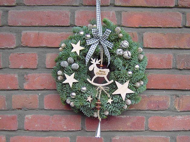 """**Türkranz Elch**  ein frisch gebundener Türkranz mit Nobilistanne. Nobilistanne hält lange und nadelt nicht.  Dekoriert mit Holzelch mit der Aufschrift """"Merry Christmas"""", Holzsterne in..."""