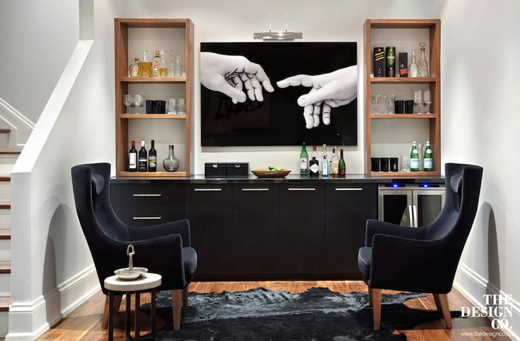 Contemporary basement with wet bar boasting black base cabinets adorned with chrome pulls and fitted with two-door glass-front beverage fridge topped with sleek black countertops topped with walnut stained shelving units filled with wine glasses and libations flanking a flatscreen TV attached to the wall illuminated by a picture light.