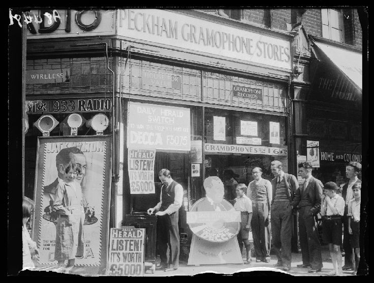 The Peckham Gramophone Store in 1932.  A poster hanging above the doorway advertises a chance to win 5000 pounds by buying a Decca F3075 record player. The men and boys stand outside the shop are listening to a record put on by the shop manager. Photograph by Leslie Cardew.